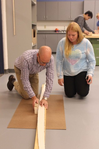 Senior Ashley F watches technical education teacher Jeremy Case demonstrate construction of her surfboard. An auction will be held in May.