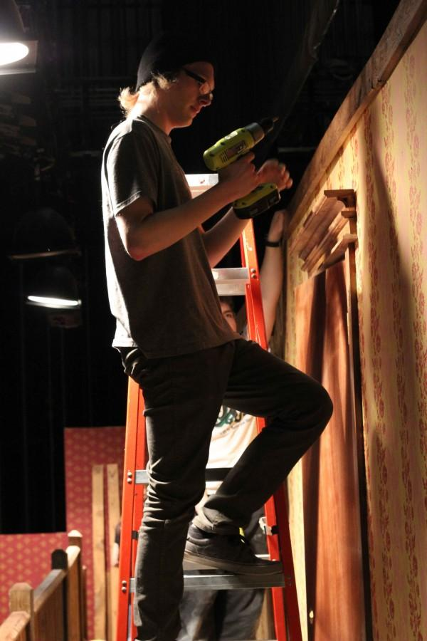 Sophomore David Slocum handles the power tools on the second story of the stage. Slocum will be performing in the show Noises Off.