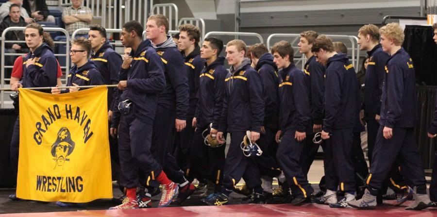 The Buccaneer wrestling squad marches around Kellogg Arena before the start of state quarterfinals. The last time the team made it to state was 2012.