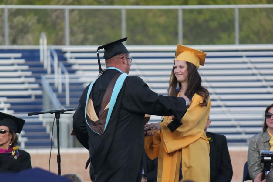 Mackenzie Burkhardt presents teacher Brian Williams with one of the faculty of the year awards.