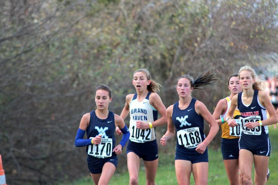 Freshman Gabby Hentemann keeps up with two runners from Waterford Mott high school at the state cross country meet on Nov. 7.