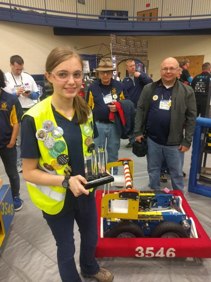 Sophomore Alexandra Holt holds a trophy in front of the team robot. They placed fourth in the district competition.