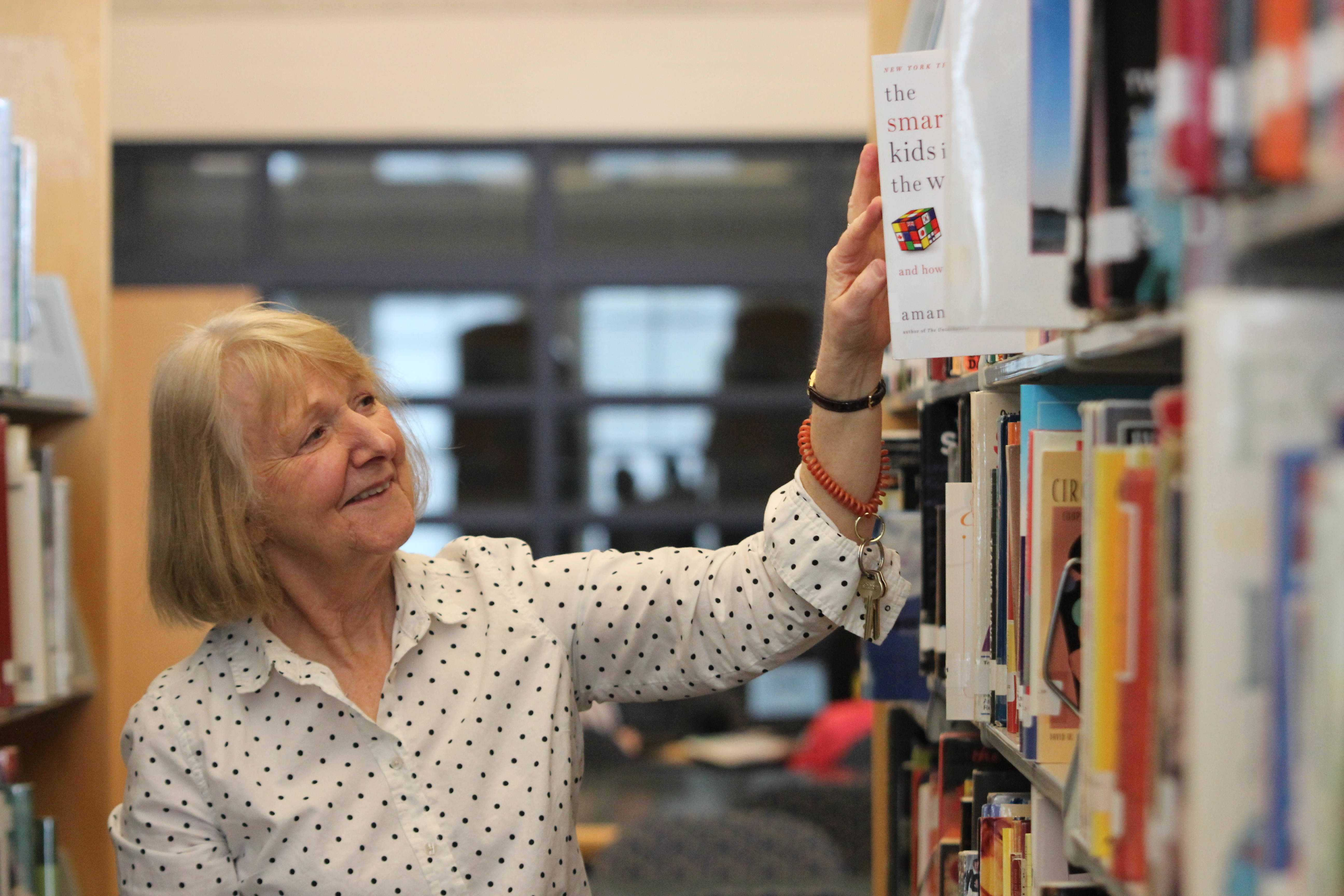 """LOOKING FOR ADVENTURE: Library media specialist Gloria Klinger places a book on the shelf. After 30 years of working in the district, Klinger's retiring. """"Even though I love my job, it's time to take off and do some travelling,"""