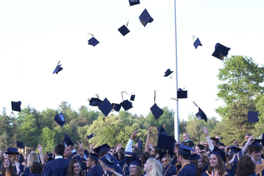 Graduates celebrate their commencement by throwing their caps into the air.