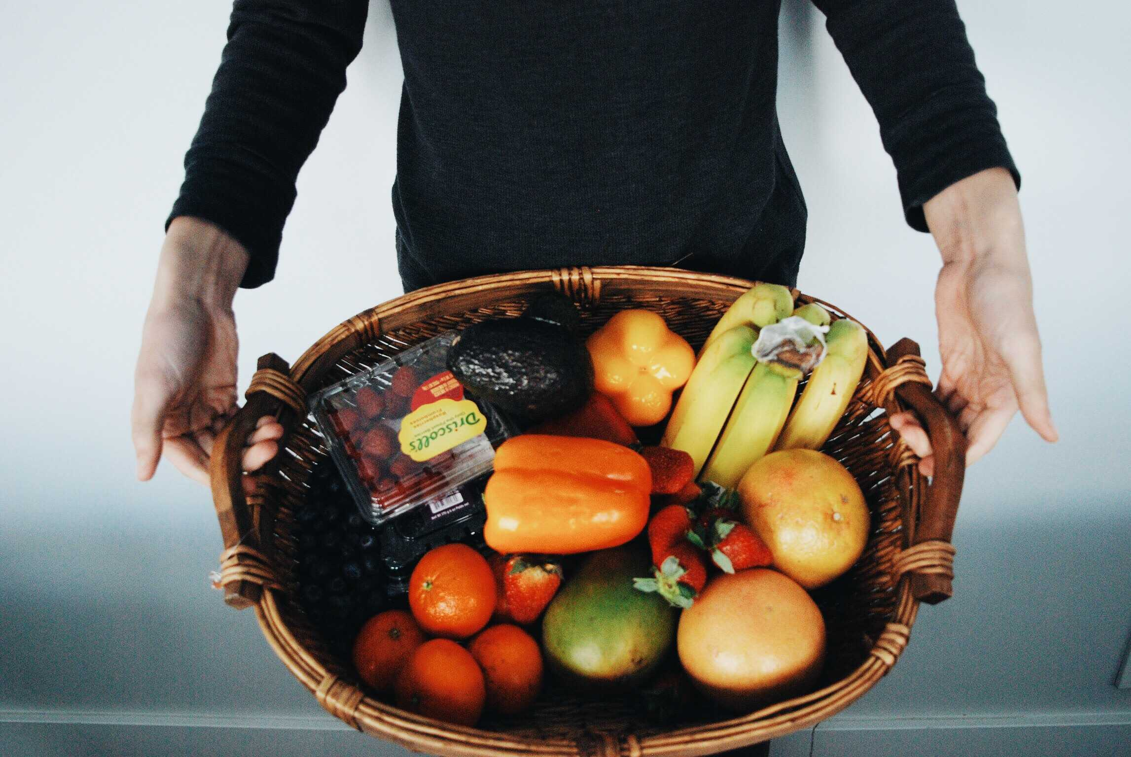 Jack Nicholson holds a basket with a variety of fruits and vegetables that could be included with every meal.