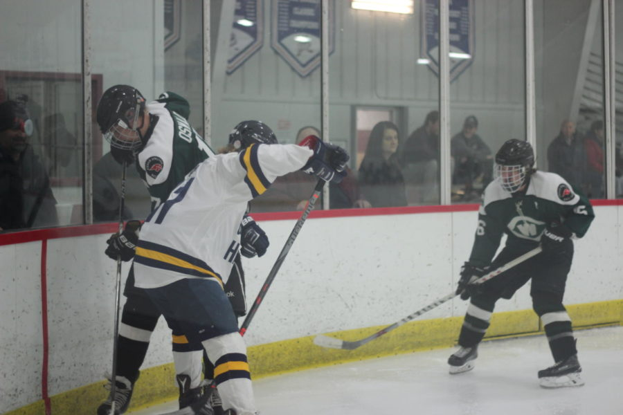 Sophomore Cooper Fox crunches a defender against the glass. Even though he is only a sophomore, Foxs talent and skill have helped the Bucs greatly this season.