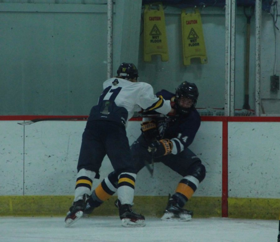 Sophomore Cooper Fox checks one of the Portage Central defenders into the boards, as Fox seemingly owned the ice the entire night, adding a goal and an assist of his own to the score sheet.