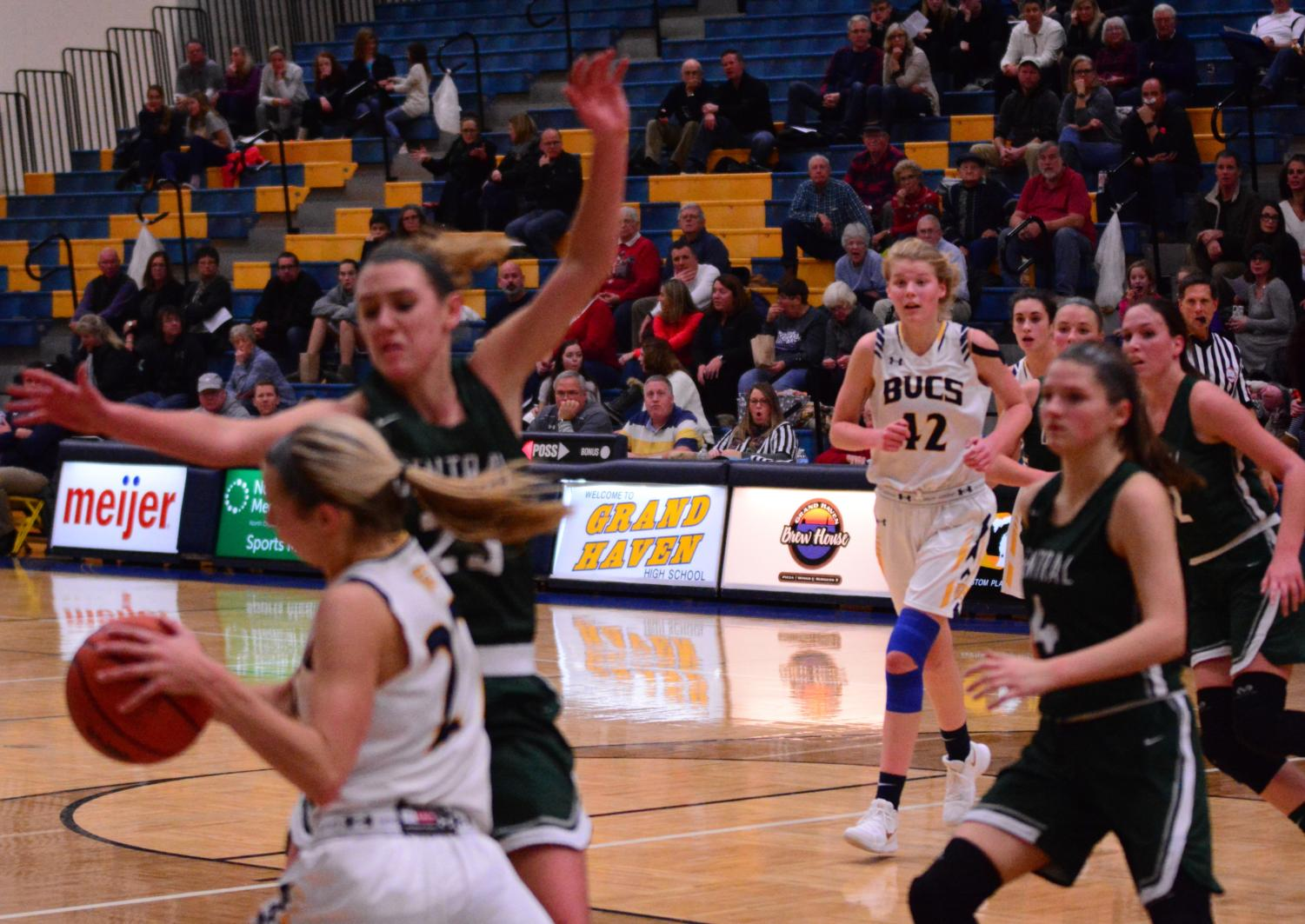 Senior Autumn Buikema looks to pass to junior Esther Byington while being heavily guarded by Forest Hills Central defenders. Buikema had a solid night with six points against the Fighting Scots.
