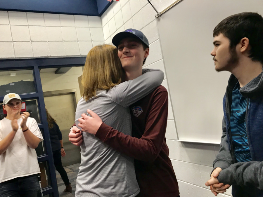 Junior Austin Craymer and biology teacher Katy Walters share a hug after the surprise party was unveiled. Students from every grade level filled the room, including teachers, parents and administration members.