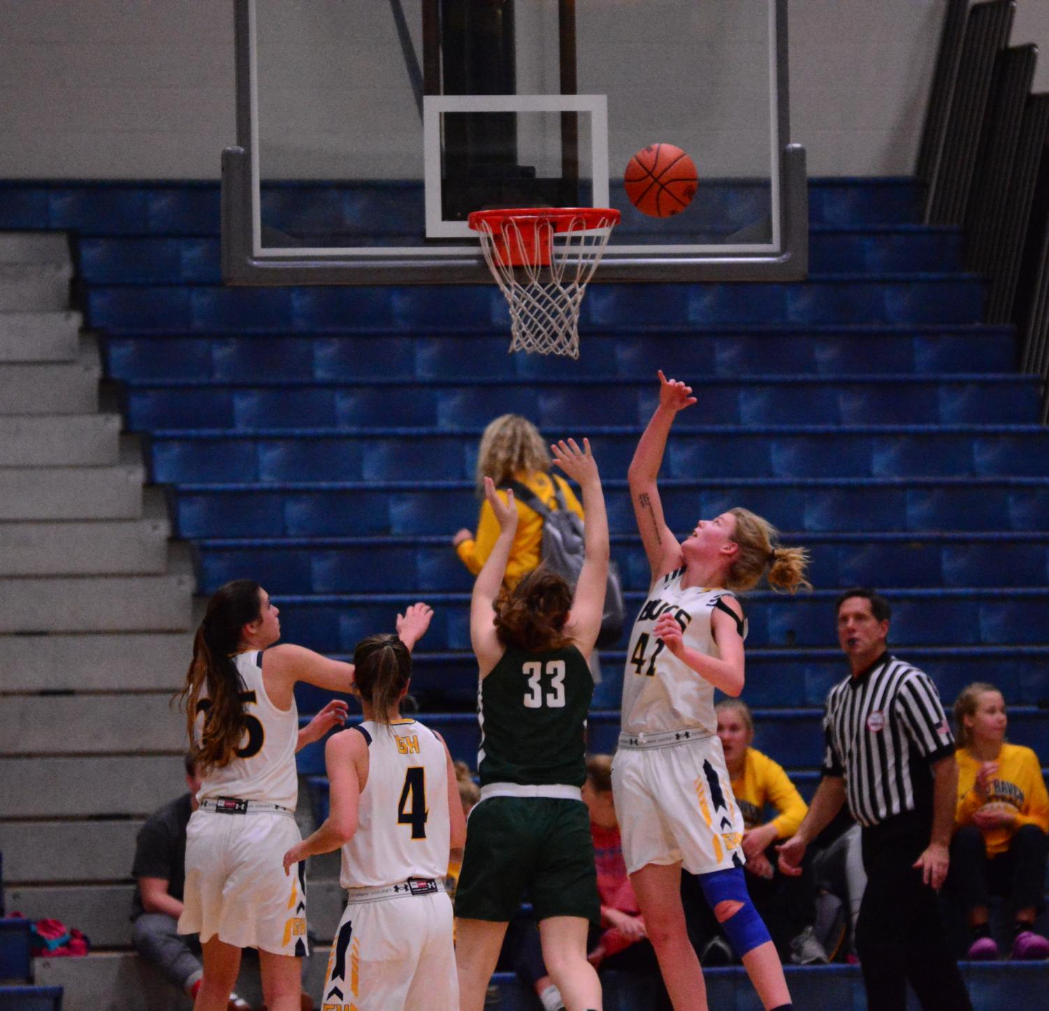 Junior Esther Byington attacks the hoop and puts it off the glass. Not many students were there to witness this great play by the junior.