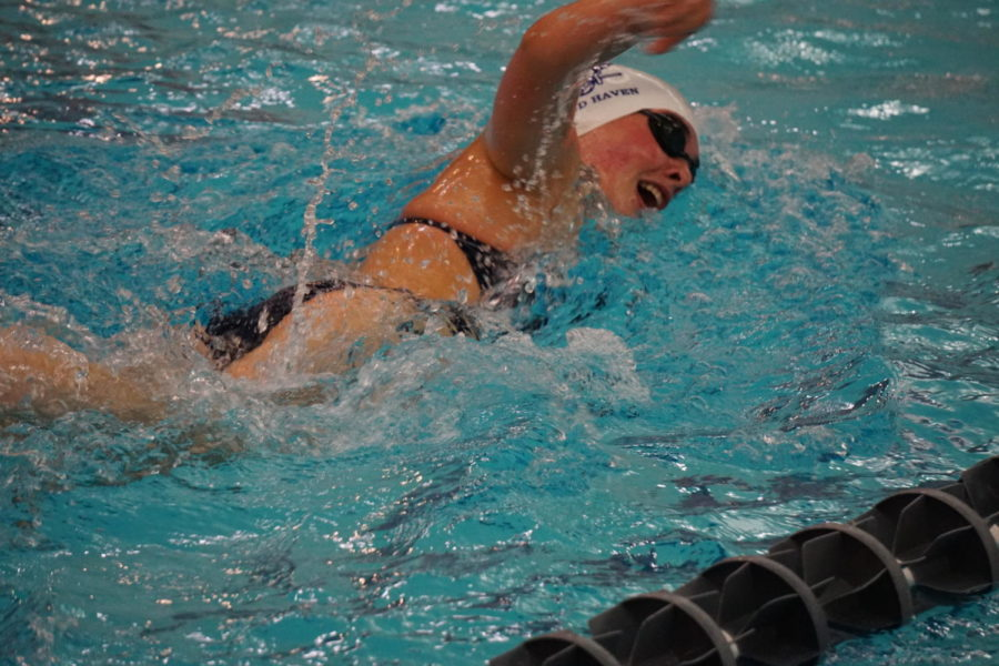 Sophomore Georgia Basil swims in a meet against East Kentwood. Basil is part of standout sophomore class that has largely propelled the program in the past two years.