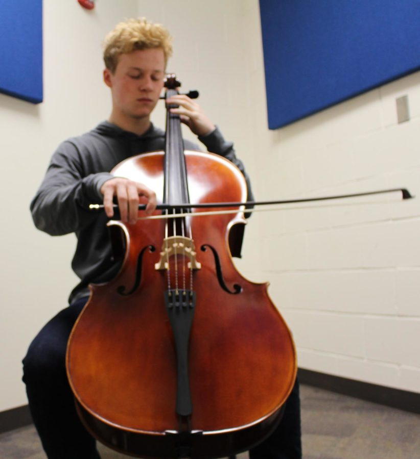Junior Keegan Young plays his cello in the practice room  during lunch. He finds cello the best instrument to connect with people because its range resembles the human voice. Young finds it important to connect with people through his music and is always trying to find more ways to connect with the audience.