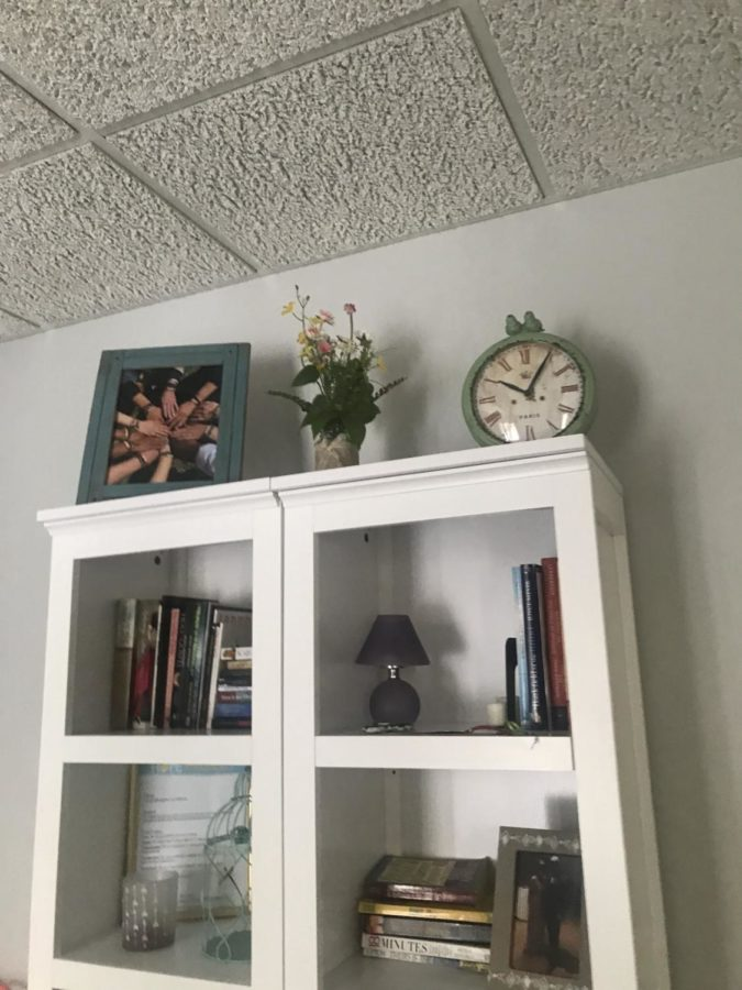 A bookshelf in the therapy room at the Hope Project. On the top sits a photo of survivors' hands showing off the bracelets they made at the survivor retreat over the summer.
