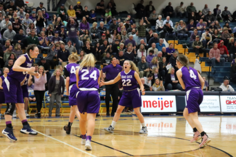 Junior Jolee Houle celebrates with her team after a high-scoring first half against East Kentwood. Houle, the team's primary outside shooter, had 18 points in a loss to Muskegon in the district opener.