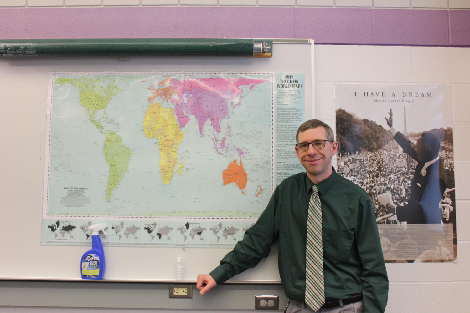 Jason Klinger poses under his world map with a smile