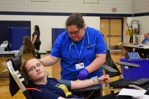 Junior Emily Stevenson gives blood. Although many people are wary of needles and blood, most students assure that the pinch was better than expected.