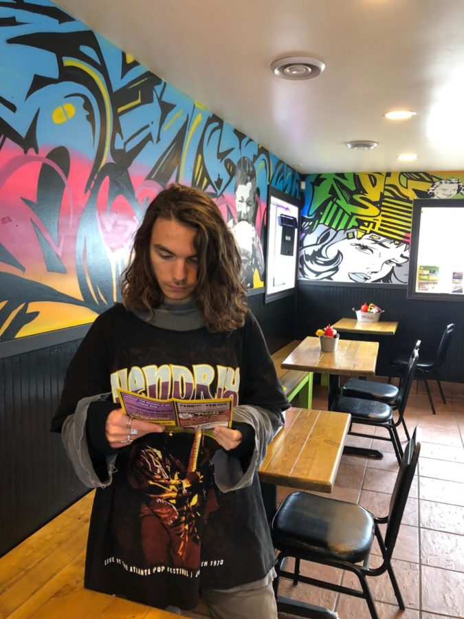 Nick+reviewing+the++menu+in+the+colorful+shop.+