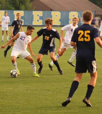 Senior Gavin Jonker battles for the ball against Caledonia. Jonker, among with the rest of the senior, have acted as leaders for a primarily young team this year.