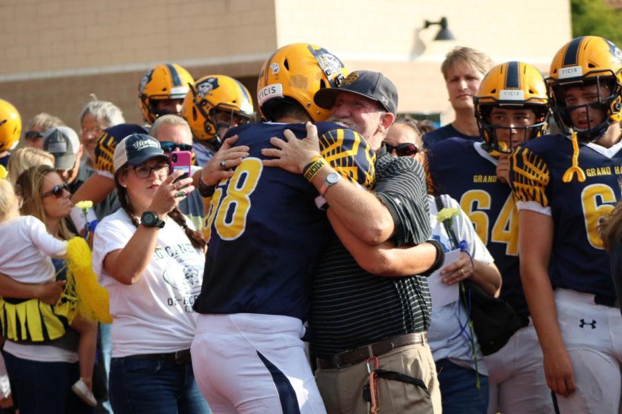 Sophomore Dayne Arnett hugs Rusty TenHagen during family night. TenHagen has been supporting the community for decades.