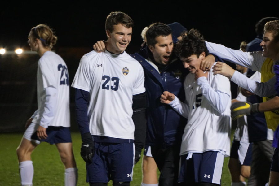 JV Coach Derek Ottenbaker smiles and hugs sophomore Brady McDonald and junior Ethan Prins in celebration of how well both of them played in the district finals. The boys varsity soccer team moved on to regional semifinals after claiming district finals.