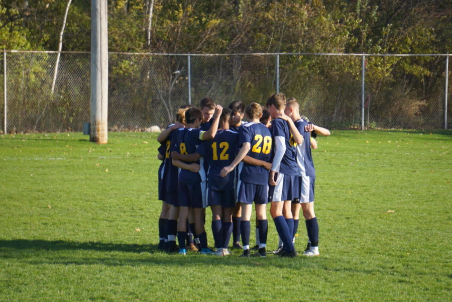 The boys varsity soccer starters huddle up before the final game of the season.