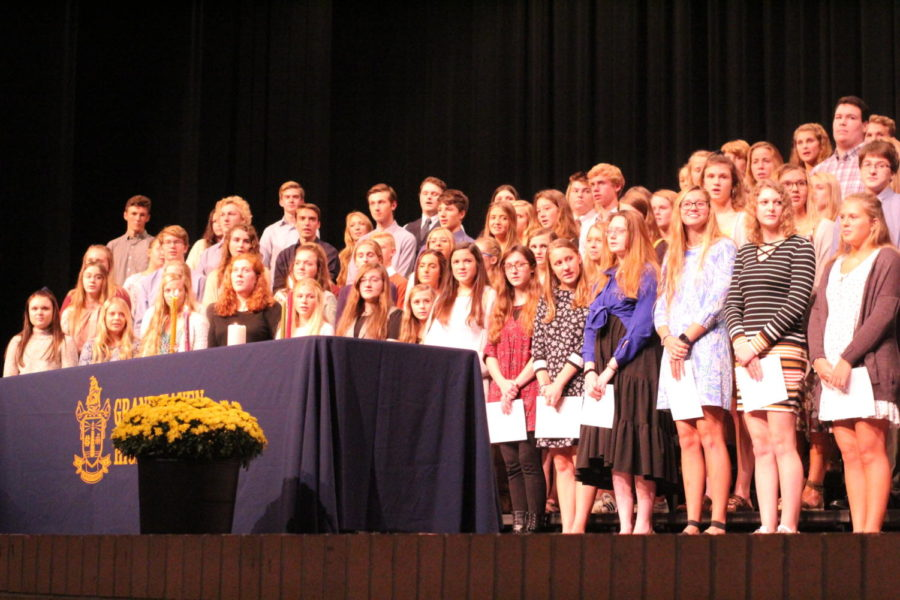 NHS inductees stand on stage after being inducted into the society.