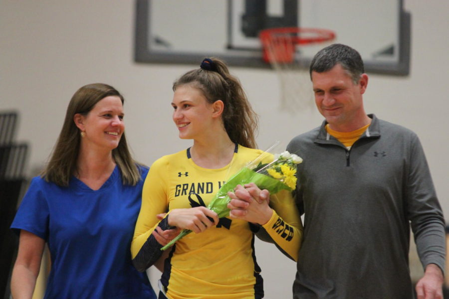 Senior Ashley Slater is accompanied by her parents as she proceeds across the court with pride.