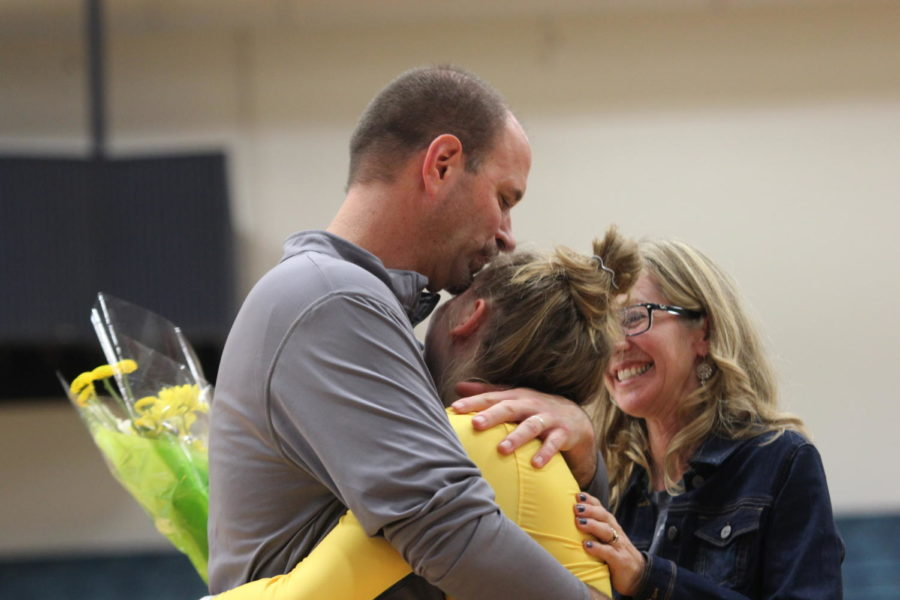 Senior Reece Redder's dad embraces her in support before the game.