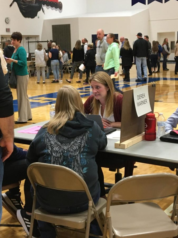 Science teacher Katy Walters conferences with parents. Teachers were dispersed throughout the gym.