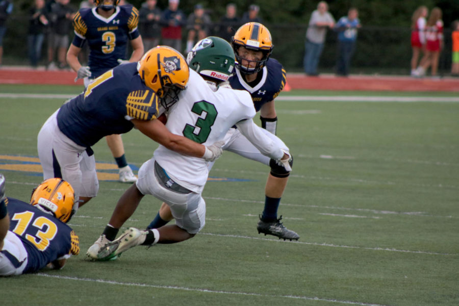 LB/TE Aidan Cooper takes down a Reeths Puffer Rocket at a home game on Sept. 13. Cooper, as well as others, have worked hard the last two years on varsity to make Grand Haven football better.