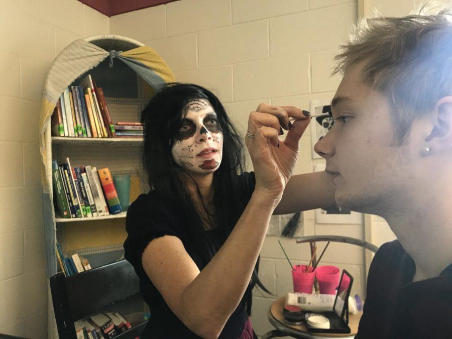Spanish teacher Penney Johnson paints half of junior Kadyn Schultz' face as a sugar skull.