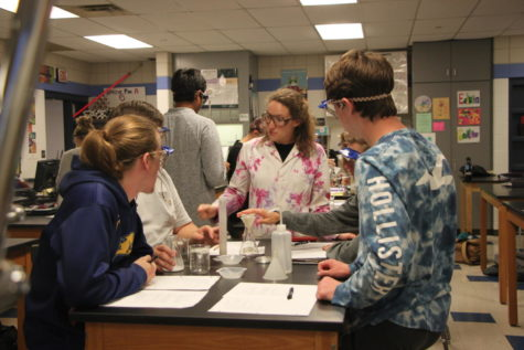 Chelsea Bender assists students with a lab in her chemistry classroom