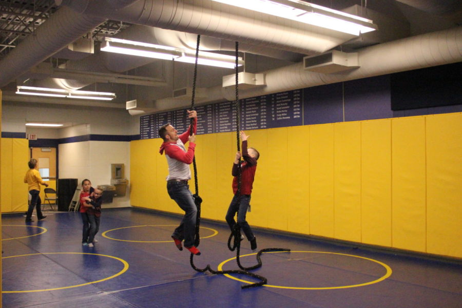 In the wrestling room, Cox relives his high school days and races his son up the ropes, showing off his superb athletic talent.