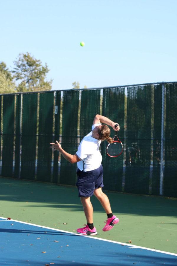 Noah Bachmann winds up during a serve at a home tennis match.