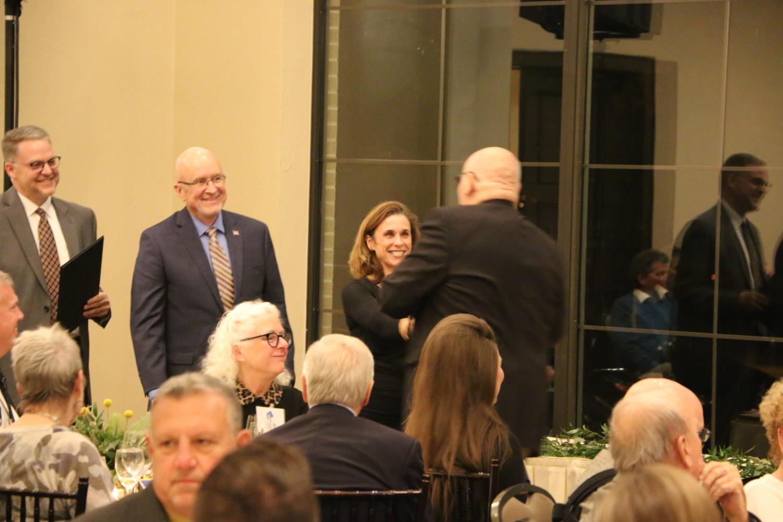 Principal Tracy Wilson congratulates inductee Gene Van Dongen after his speech.