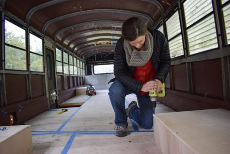 Laura Knochenhauer works on the interior of her family's bus. Right now it appears to be nothing more than plywood and tape, but soon it will be a fully functioning family home.