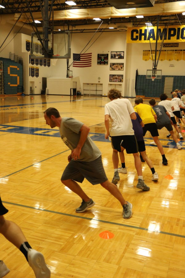 Boys varsity basketball coach Greg Immink runs with the team during tryouts. The weeks of practices all lead up to the squad's first game against Reeths-Puffer.