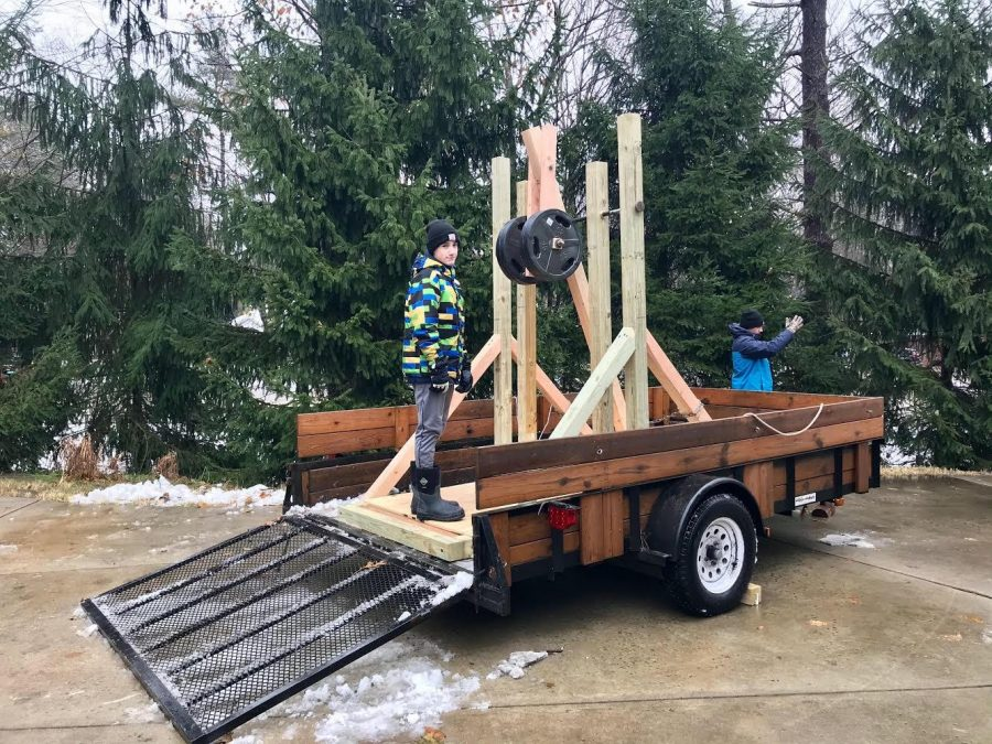 """Freshman Grant Taylor climbs on top of the trailer holding the trebuchet he made with his dad. """"After doing the project and seeing how everything worked, it was weird how it actually works,"""" Taylor said. """"Like actually being able to see it throw over and see the counterweight active and see how it drags."""""""
