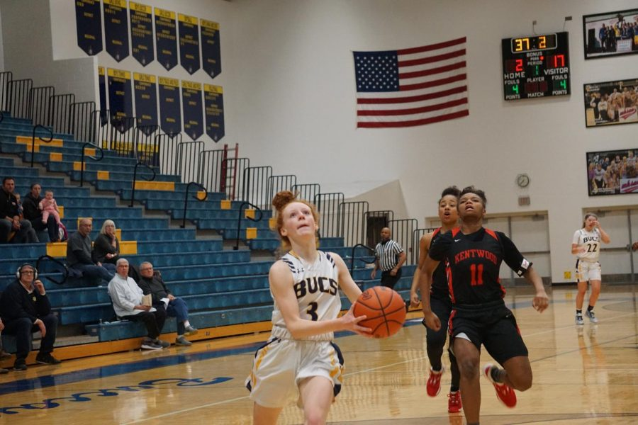 Sophomore Alyssa Hatzel goes in for a lay up to get another bucket for the Bucs. The girls varisty basketball team lost against East Kentwood on Tuesday, Jan. 28.