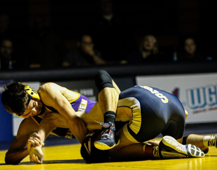 Freshmen Bode Wilson has his arms and legs wrapped   Hudsonville's competitor, locking him in a dead lock.