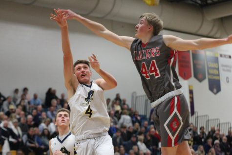 Senior Adam Strom takes the ball to the basket with a defender on his heels in the Battle of the Bridge game. The area around the basket was huge in this game as the squad fought for rebounds all night.