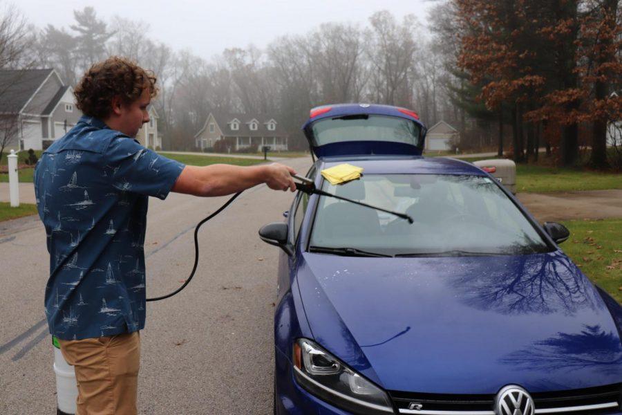 Junior+Mason+Milligan+sprays+clean+a+car+using+a+pressure+washer.