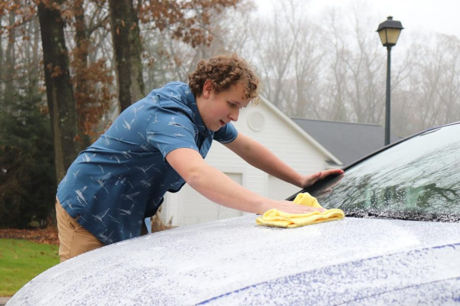 A piece of cloth is used to wipe down the car from the soapy exterior.