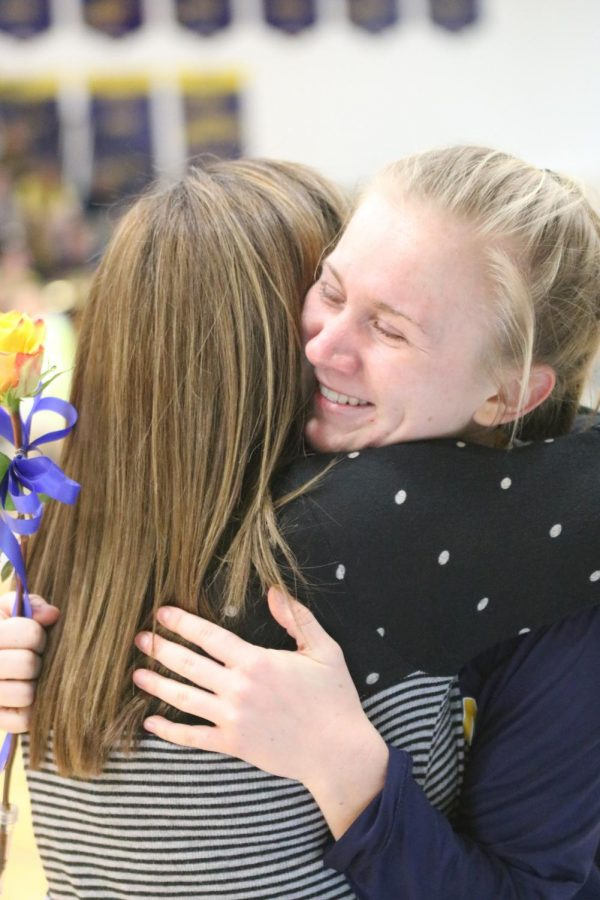 After receiving her flower, senior Morgan Goss smiles while hugging Coach K on senior night.