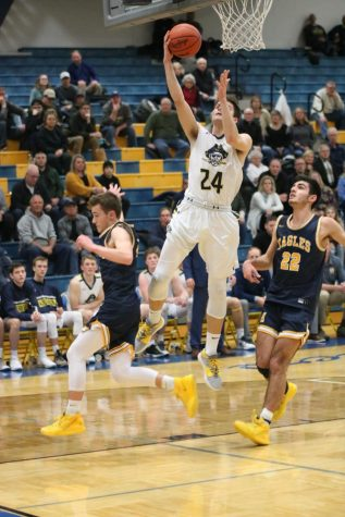 Owen Ross goes up for a layup during a conference rivalry game against Hudsonville.