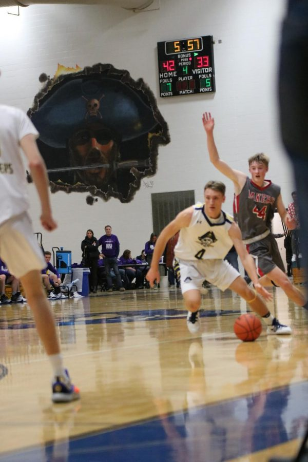 Senior Adam Strom dribbles the ball up the court against Spring Lake on December 20. Strom, who is a senior leader on the team, will be an important factor in the team's game plan Friday.