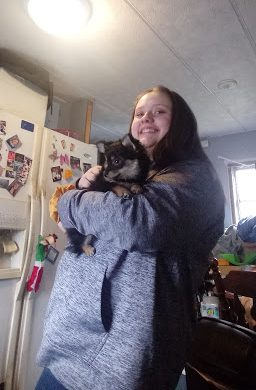 Sophomore Ellie Guilford holds up her dog, Melaina. The break from school helped her make more time to spend with her pets and family.
