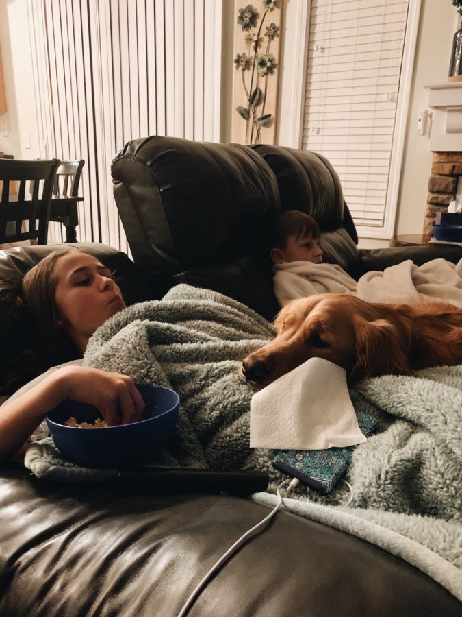 Junior Makenna Edwards relaxes on her couch with her younger brother Aiden and her dog Charlie.