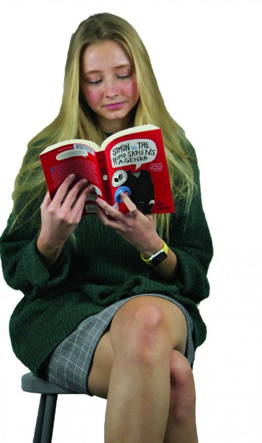 Senior Katie reads Simon and the HomoSapiens Agenda which was later produced into the movie Love, Simon. When Weigle was exploring her identity as a member of the LGBTQ community, she was able to turn to some of the literature at Lakeshore Middle School which helped her reaffirm her actualization and gave her a figurative mirror for her to look into.