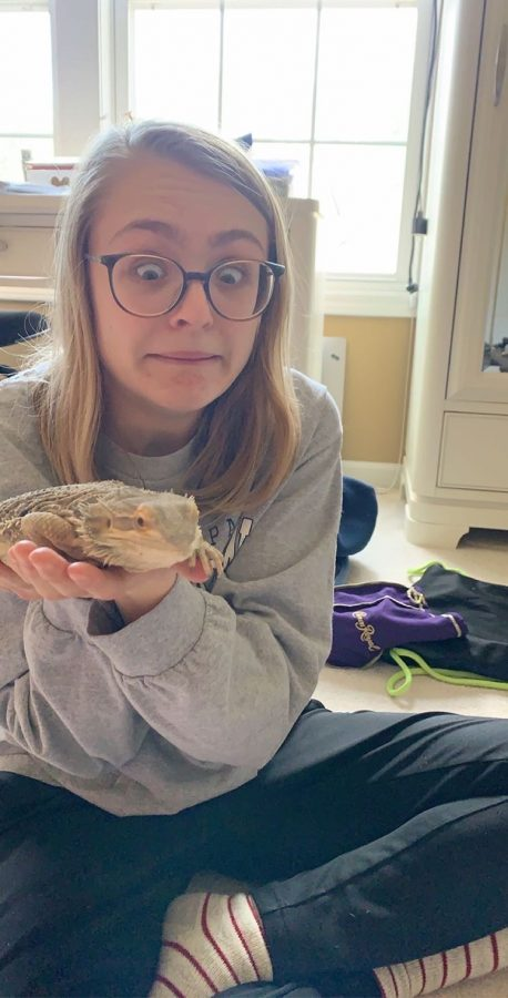Junior Alexis Mountford plays with her brother's bearded dragon, Magma, during her time off school